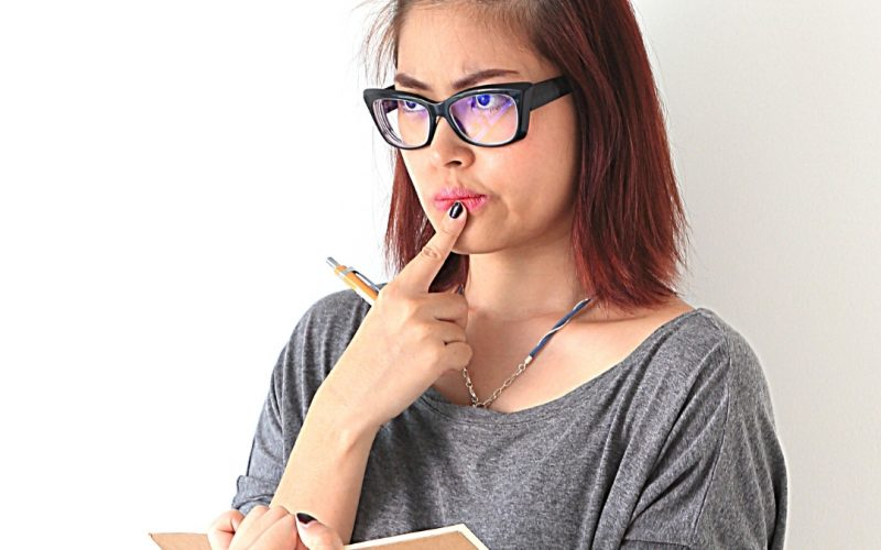 Image: Woman holding planner and pencil with a thinking look.