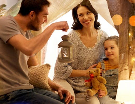 Family of 3 in a blanket fort