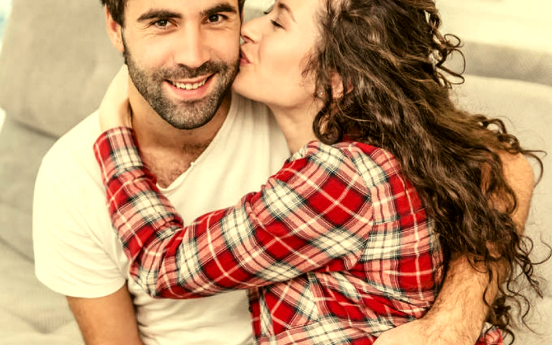 Happy couple sitting on couce as she kisses his cheeck from blog Secrets to Having a Long-lasting Marriage | GreatPeaceLiving.com #marriagemoments #marriage